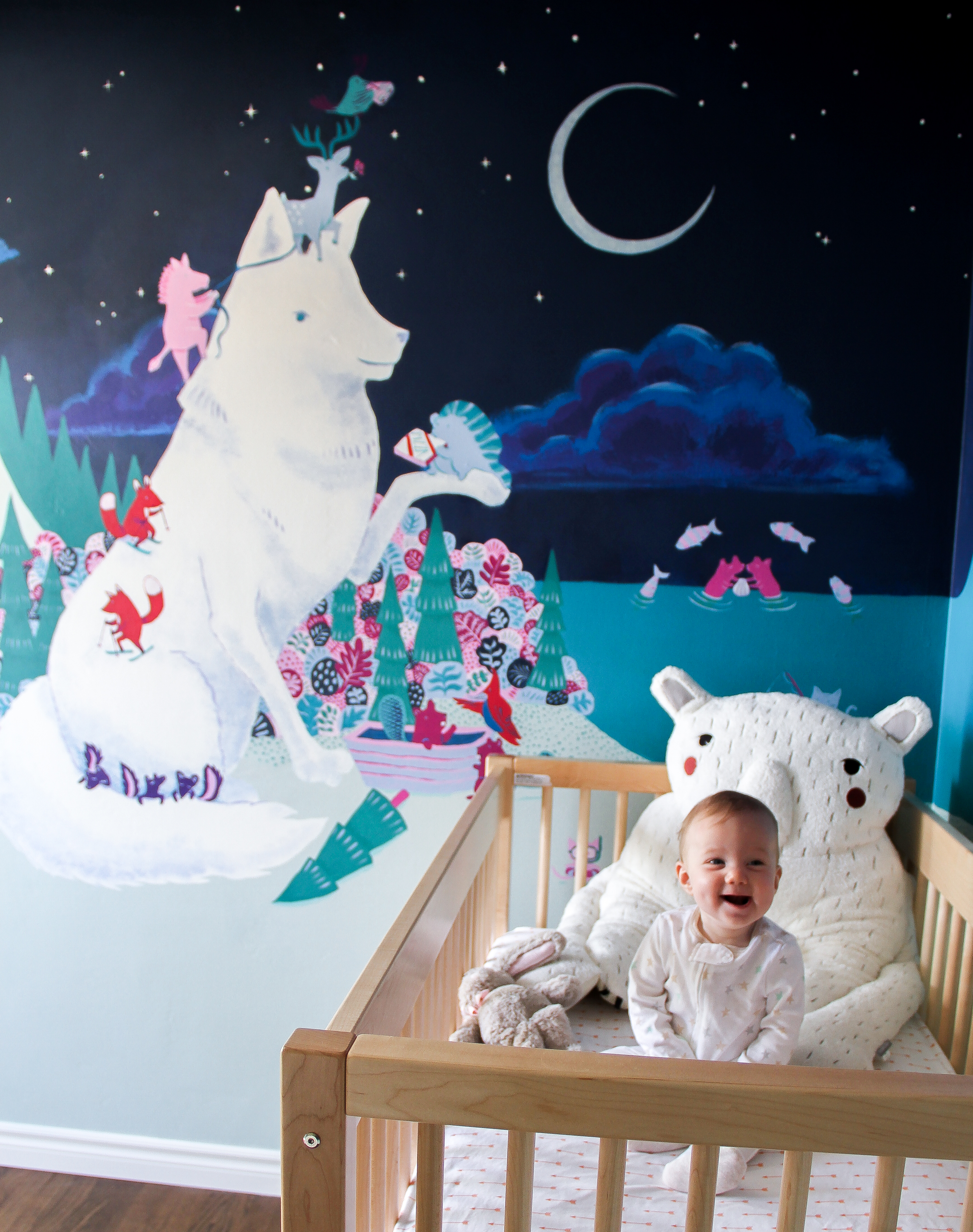 Baby Madeline in her crib with mural behind